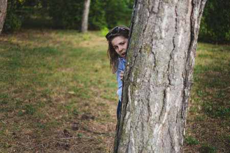 Scared girl hiding behind a tree trunk - Frightened caucasian woman peeking while being outside in a forest