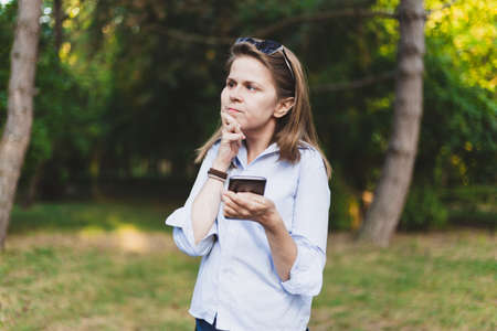 Girl holding a phone while holding her hand on chin - Expressive student thinking outside in campus - Woman in doubt with smartphone in her palm