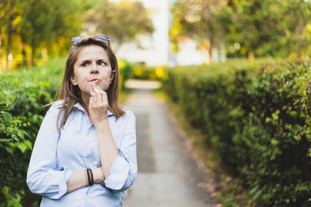 Business woman thinking outside - Thoughtful person holding hand on the chin - Pensive attractive lady looking up and wearing a blue shirt and sunglasses on head