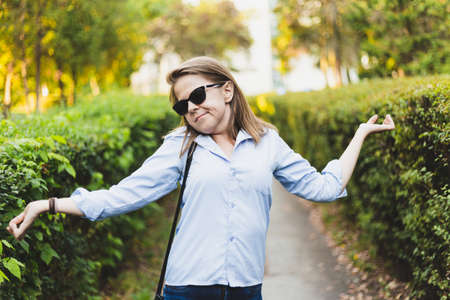 Doubtful young woman raising her shoulder outdoors - Cute girl with brown hair wearing sunglasses wondering and questioning things while walking in the park