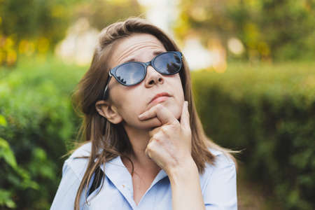 Businesswoman thinking at something while wearing sunglasses and watching above her - Lonely depressed teen person being contemplative outside