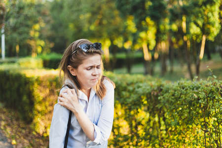 Young woman holding her painful shoulder outside in a park - Pretty lady with brown hair suffering from muscle cramps while walking in nature Foto de archivo