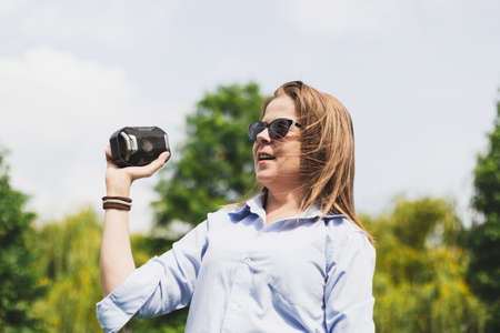 Happy beautiful young woman holding small portable speaker outdoors on a summer day - Smiling cute girl with brown hair wearing sunglasses singing while listening to music in the park Foto de archivo