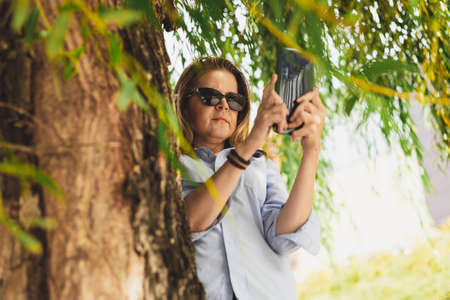 Pretty woman wearing sunglasses taking a photo with a mobile phone outside on a summer day - Casually dressed girl with brown hair using technology in nature while sitting next to a tree in the park Banque d'images