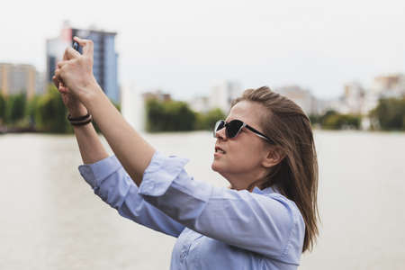 Woman taking selfie picture outside - Business lady with sunglasses taking a shot with her phone camera near a lake