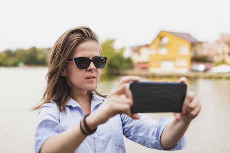 Young vlogger recording a video for her next social media event - Teen holding mobile camera horizontally while recording her talking outside