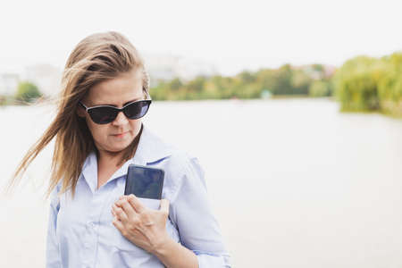 Woman with phone in pocket - Business lady with sunglasses grabbing her smartphone from her shirt - Girl holding huge mobile device