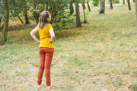 Lost woman in the forest looking in the distance for a way out – Casually dressed girl with colorful outfit standing with her hands on her hips in nature