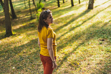 Young woman walking in the woods alone in the sun - Beautiful girl with brown hair feeling lost in the forest on a summer day - Casually dressed female daydreaming in nature Foto de archivo