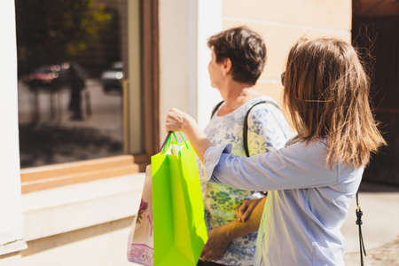 Mother and daughter spending earnings together. Granddaughter pointing at a retailer window. Feminine shopper having fun in front of a supermarket Banque d'images