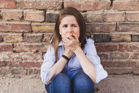 Scared woman sitting on the ground while leaning with elbows to her knees against a brick wall and looking to the camera - Frightened young girl holding her hands to the mouth