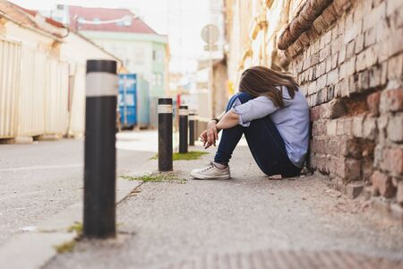Sad young woman sitting alone on the concrete in the city with her head on her knees - Stressed casually dressed female worker feeling anxiety outside - Concept image for domestic abuse