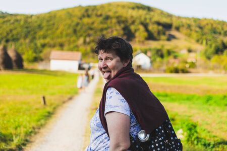 Happy senior woman acting crazy while showing tongue in nature - Cute old lady with brown hair having fun and feeling good outside - Concept image for joyful life