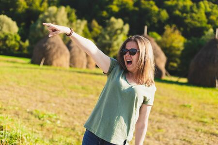 young woman pointing and yelling while walking in nature on a sunny day - Angry cute girl wearing sunglasses screaming in nature while showing with one hand Фото со стока