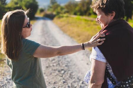 Daughter consoling and supporting her mother while walking in nature on a summer day – Girl listening to pretty old lady while holding a hand on her shoulder Фото со стока