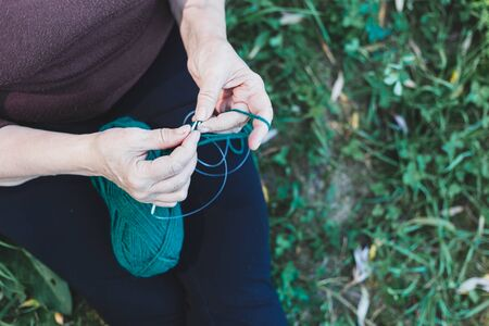 Close-up shot of senior woman's hands knitting outside while sitting on grass - Elderly person with a fun and relaxing hobby - Practical and useful activity