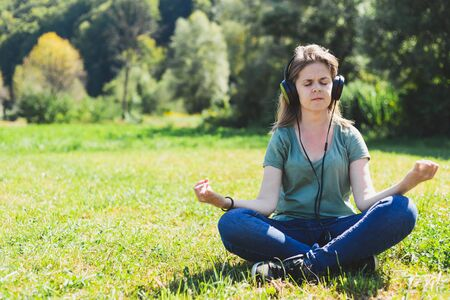 Young woman sitting in a lotus yoga position on the grass in nature on a summer day – Girl with brown hair relaxing outdoors while listening to music on a pair of big headphones Stok Fotoğraf
