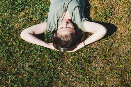 Young woman lying on the grass whit hands under her head on a summer day – Pretty girl with brown hair relaxing in nature while listening to music on a pair of headphones