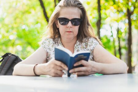 Bible study concept of one young woman with sunglasses - Student studying outside with a small blue book cover in her hands