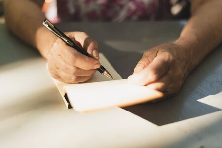 Woman taking notes - Close-up to female hands holding a pen and a notebook - Journalist writing at interview