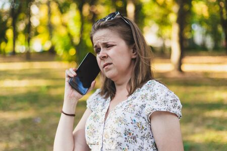 Frowning young woman talking on mobile phone outside – Angry casually dressed girl with brown hair having a rough conversation at the cellphone