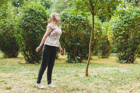 Woman breathing fresh air - Girl enjoying the calm and the smell of nature while being carefree outside