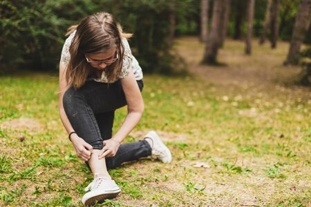 Woman doing a skin check on her feet - Girl inspecting her dermatological condition on her ankle while being outside Reklamní fotografie