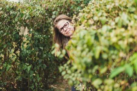 Woman hiding behind a bush - Nerd girl smiling while being behind leaves outside - Paparazzi concept image