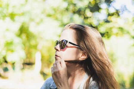 Playful woman twirling hair while wearing sunglasses - Pretty girl being seductive while playing with her strand outside