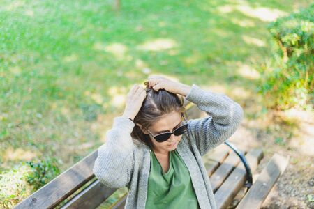 Woman fixing hair outside while sitting on a bench - Girl with sunglasses doing a hairdo to give herself a more attractive look
