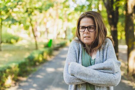 Trembling beautiful young woman freezing outside - Pretty girl wearing eyeglasses and a grey bulky sweater feeling cold while walking in the park