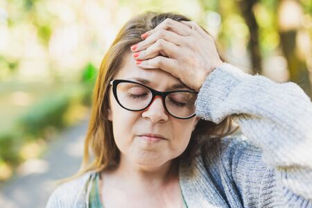 Portrait of a young woman with headache holding one hand over her forehead outside - Stressed and sad girl wearing eyeglasses feeling tired while resting in the park
