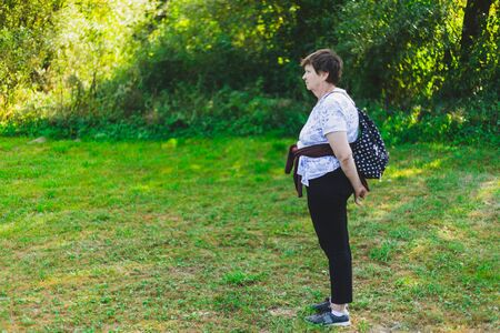 Relaxed senior woman hiking alone in nature on a beautiful summer day – Pretty old lady walking outdoors - Pleasant and fun activity for elderly persons