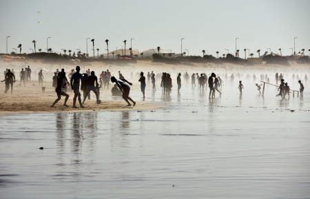 Silhouettes of various people playing football, walking and running at the beach covered with fog Stock Photo