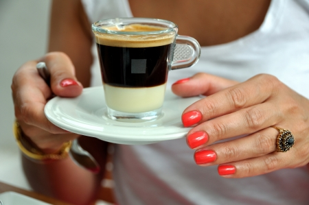 Beautiful woman Hands with ring holding a cup of coffee photo