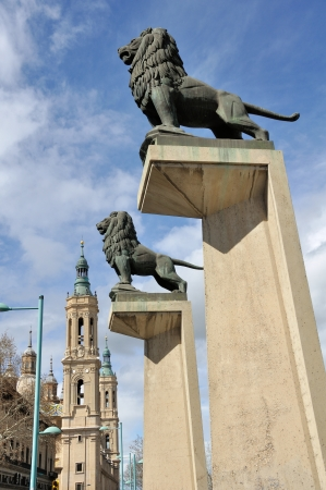 Lion statue with Basilica of Our Lady of Pillar at the background, Spain, Europe