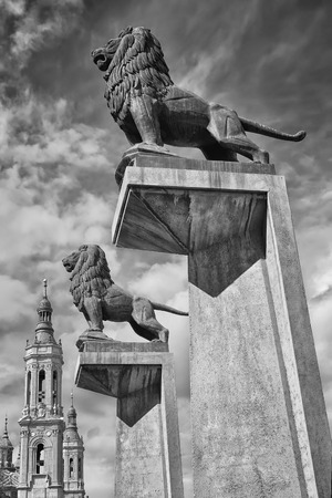 Lion statue with Basilica of Our Lady of Pillar at the background, Spain, Europe photo