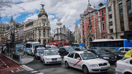 MADRID - APRIL 11, 2013: View of Gran Via street with cars and people. Famous building Metropolis - an office building and a symbol of the modern city