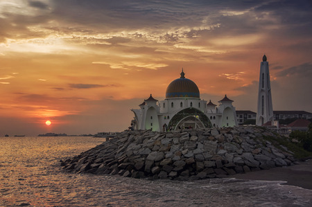 straits: Malacca Straits Mosque at sunset in Malaysia located in a man-made island. It is a relatively new and very colorful mosque opened in 2006.