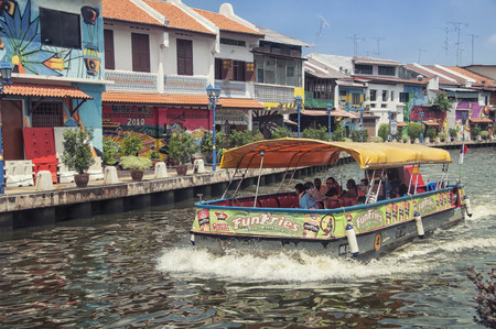MALACCA, MALAYSIA - MAY 5, 2014: River boat with tourists in the historical part of the old malaysian town. It is listed in UNESCO World Heritage Site