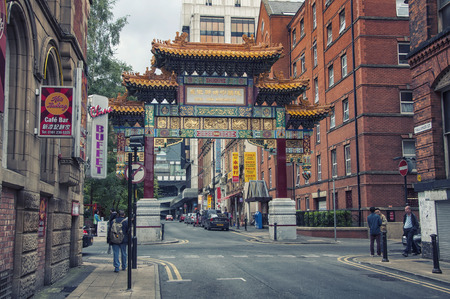enclave: MANCHESTER, UK - SEPTEMBER 3, 2014: Archway on Faulkner Street at Chinatown - an ethnic enclave in the city centre. First settlers arrived in early 20th century. Now it has many restaurants and bars.