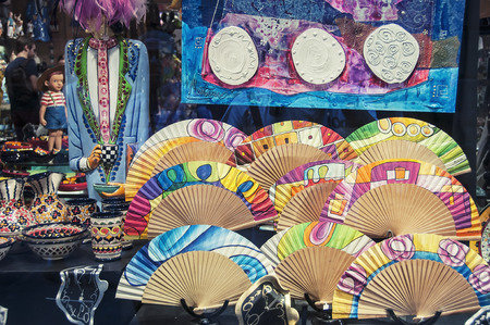 BARCELONA, SPAIN - SEPTEMBER 15, 2013: Souvenir shop in the Old Town. Different typical spanish colorful souvenirs - hand-held fans, craft, ceramics, plates and cups.