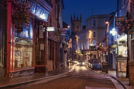 ENNIS, IRELAND - SEPTEMBER 12, 2014: Nightlife at the medieval old part of the popular touristic city in Mid-West Region. It hosts many restaurants and bars, blurry people at the street Editorial