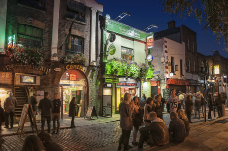 DUBLIN, IRELAND - SEPTEMBER 9, 2014: Nightlife at popular historical part of the city - Temple Bar quarter. The area is the location of many bars, pubs and restaurants Editorial