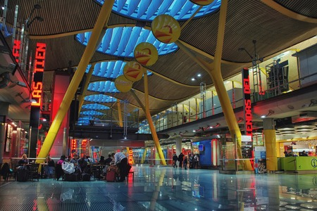 barajas: MADRID - MARCH 29, 2011: Interiors of Terminal 4, Adolfo Suarez Barajas International Airport, the main airport in Spain. Duty free shops, restaurants and people waiting for their flights