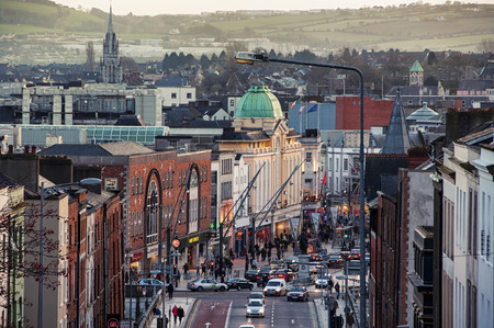 CORK, IRELAND - DECEMBER 7, 2014: City center with various shops, bars and restaurants. Car traffic and people at the street. Mountains at the background