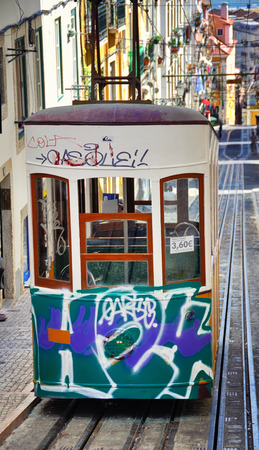 bica: LISBON, PORTUGAL - JULY 24, 2013: The Bica Funicular painted in graffiti - the symbol of the city, operating since 1892. Designated as National Monument
