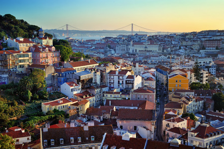 Aerial view of Lisbon, Portugal at sunset. Viewpoint Miradoura Da Graca - one of the best in the city and very popular among tourists. Bridge of 25 April at the background