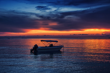 phangan: Sunset over the sea at amazing Ko Phangan in Thailand with a single boat Stock Photo