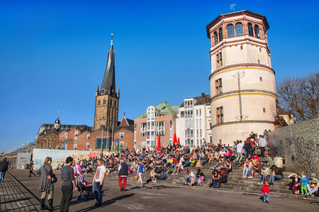 altstadt: DUSSELDORF, GERMANY - MARCH 20, 2014: Crowd of people sitting at the steps in front of Schlossturm in Altstadt in the sunny spring day.